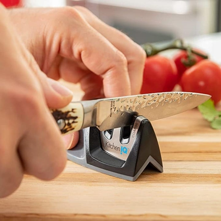 A hand swiping a knife through the black knife sharpener