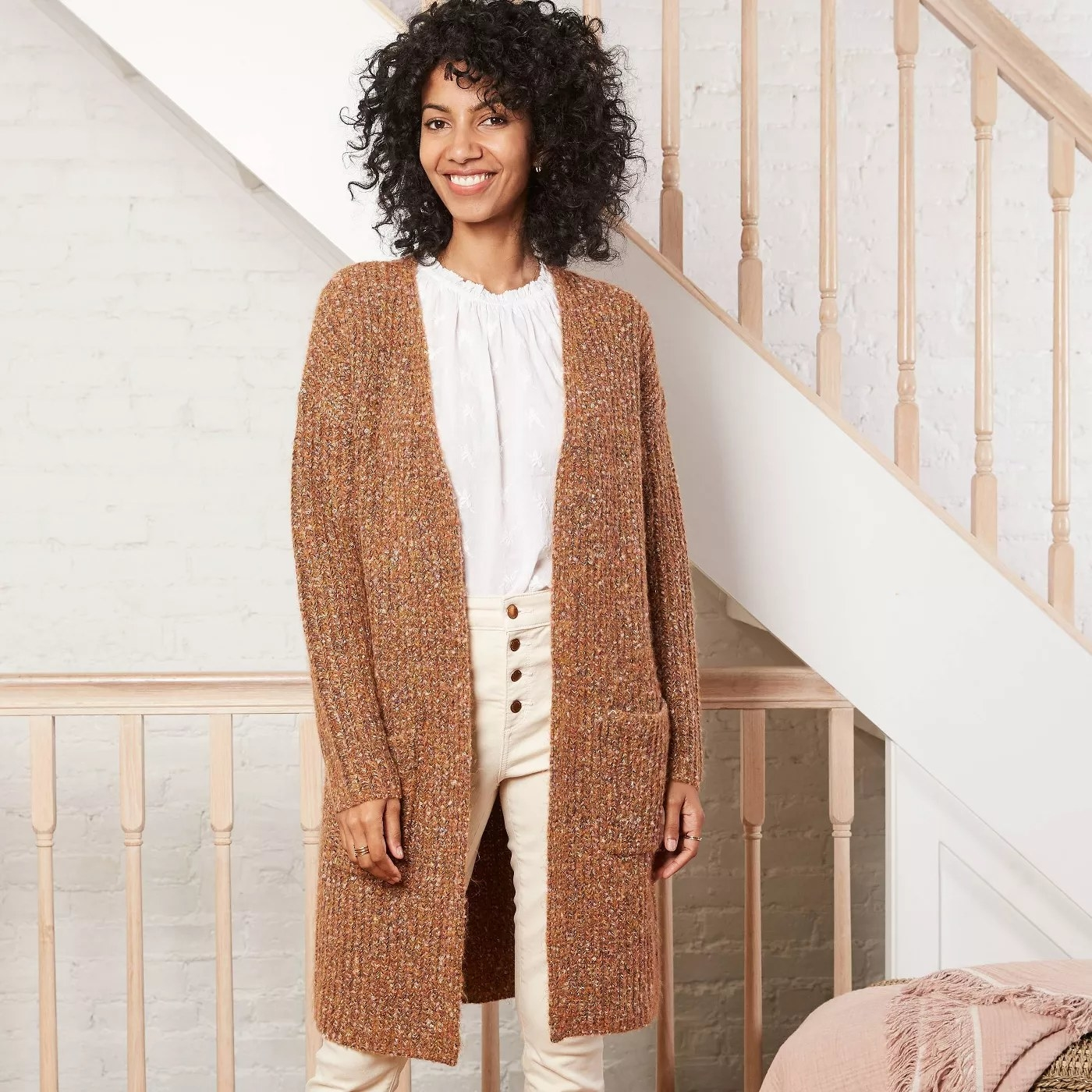 Camel colored Knitted duster that is knee length. Paired with high waited pants and white blouse.