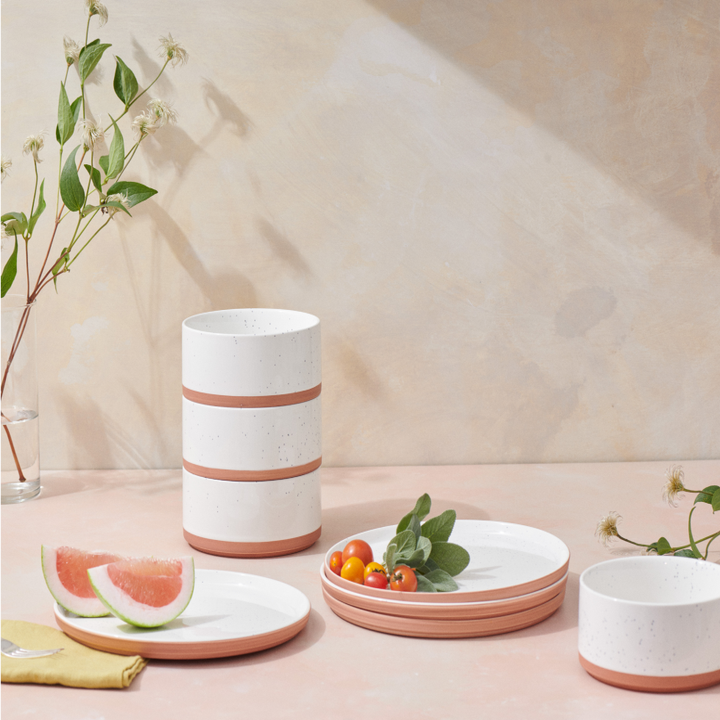 A set of plates and bowls in white with peach-colored trim and bottoms