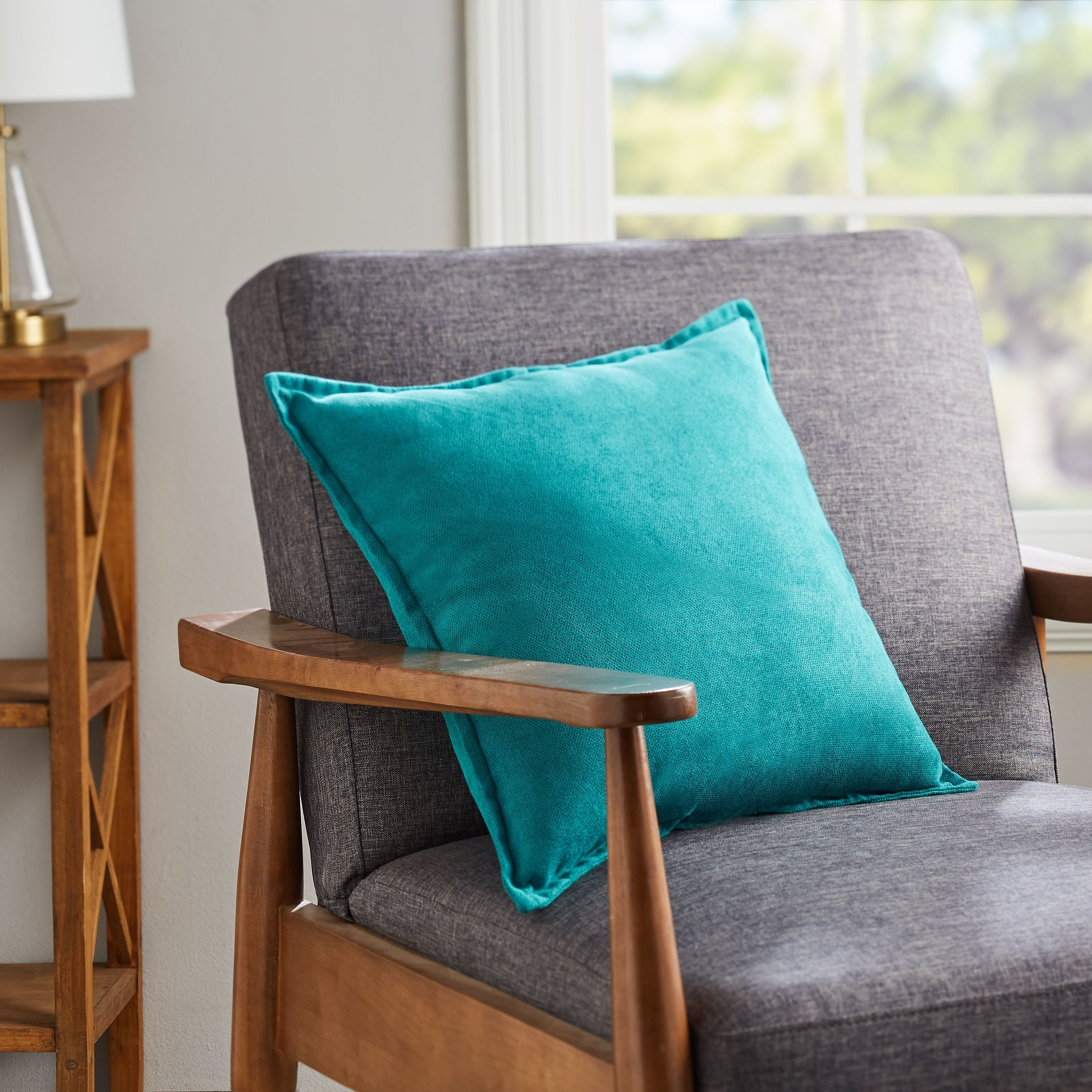 A chair with a bright blue pillow on it