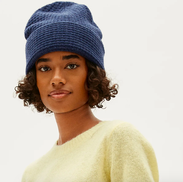 Person wearing knitted beanie over curly hair