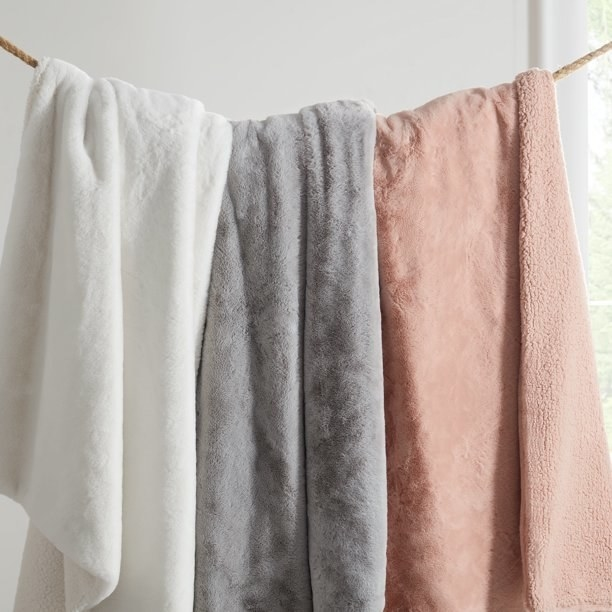 Three faux fur blankets in white, grey and pink