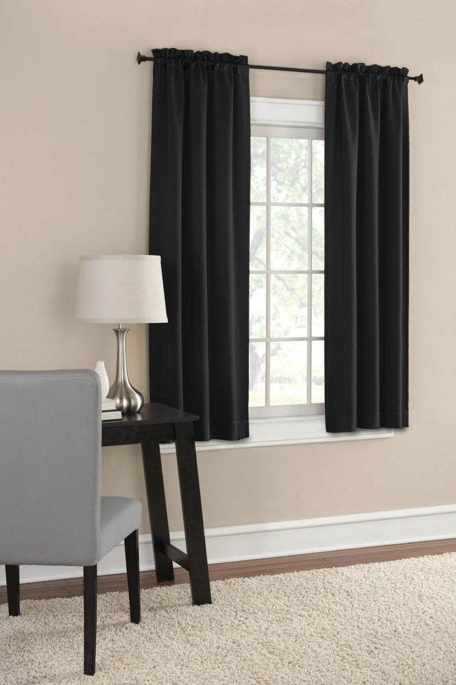 Black curtains hanging in a room