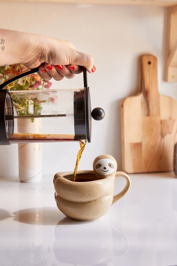 coffee being poured into the sloth-shaped mug