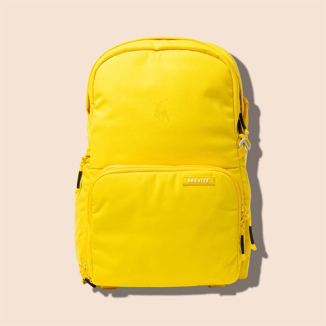 The backpack in bright yellow with front pocket and zippered pocket on the top and sides