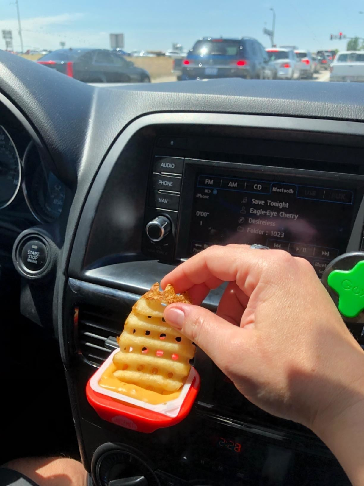 Reviewer dips french fry into honey mustard sauce in red Saucemoto dip cup