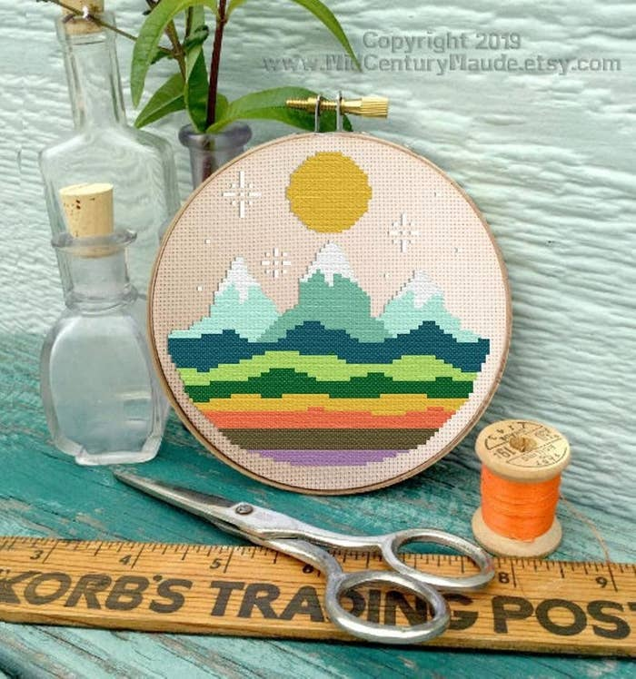 a cross stitch with a pattern of mountains