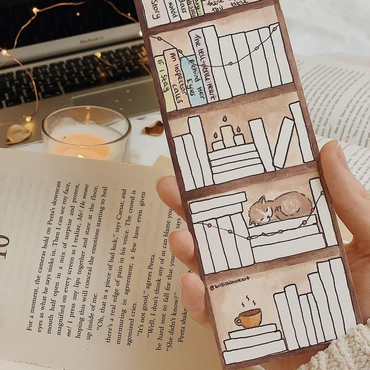 a hand holding the same bookmark with some of the blank spaced filled in