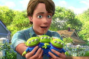 Andy holding up three little green aliens