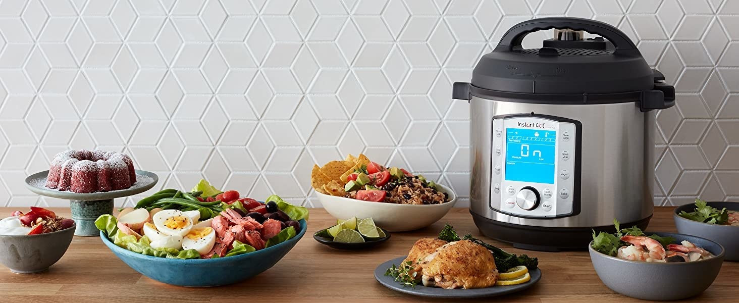 Instant Pot sitting on a countertop among an array of different prepared food dishes