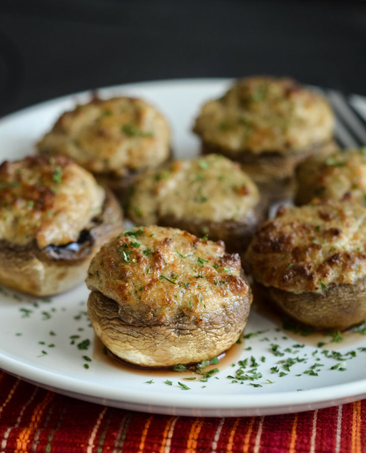 A plate of stuffed cheesy mushrooms with herbs.