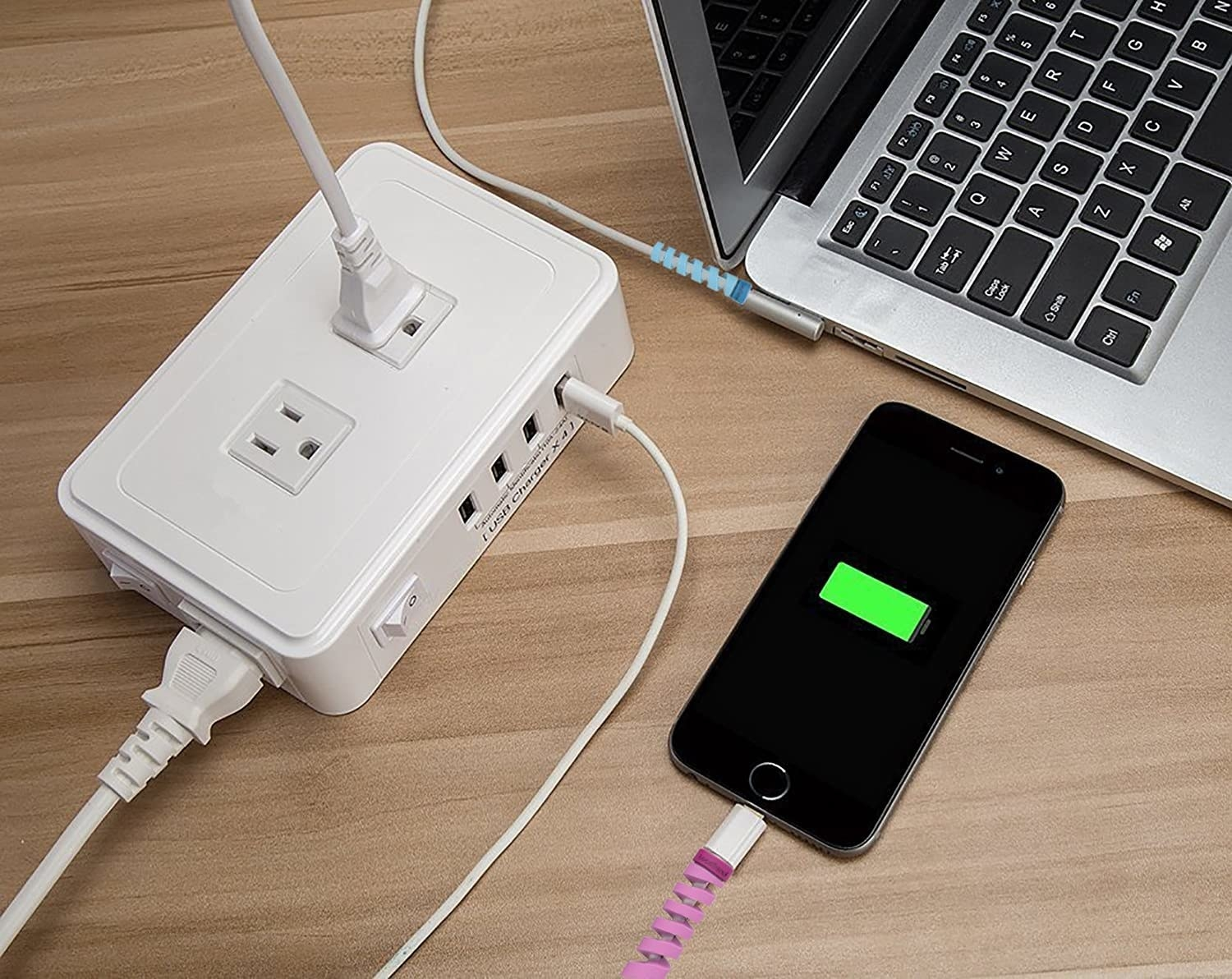 a laptop and a phone being charged by cords with cable protectors attached