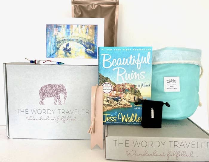 A book, postcard, and other items sit atop a wordy traveler box