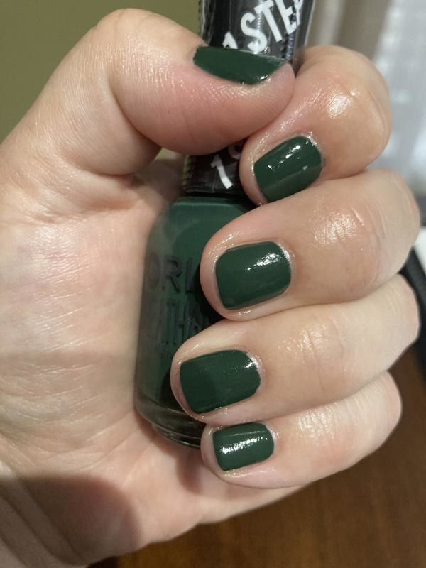 a hand with freshly painted pine green nails holding the polish