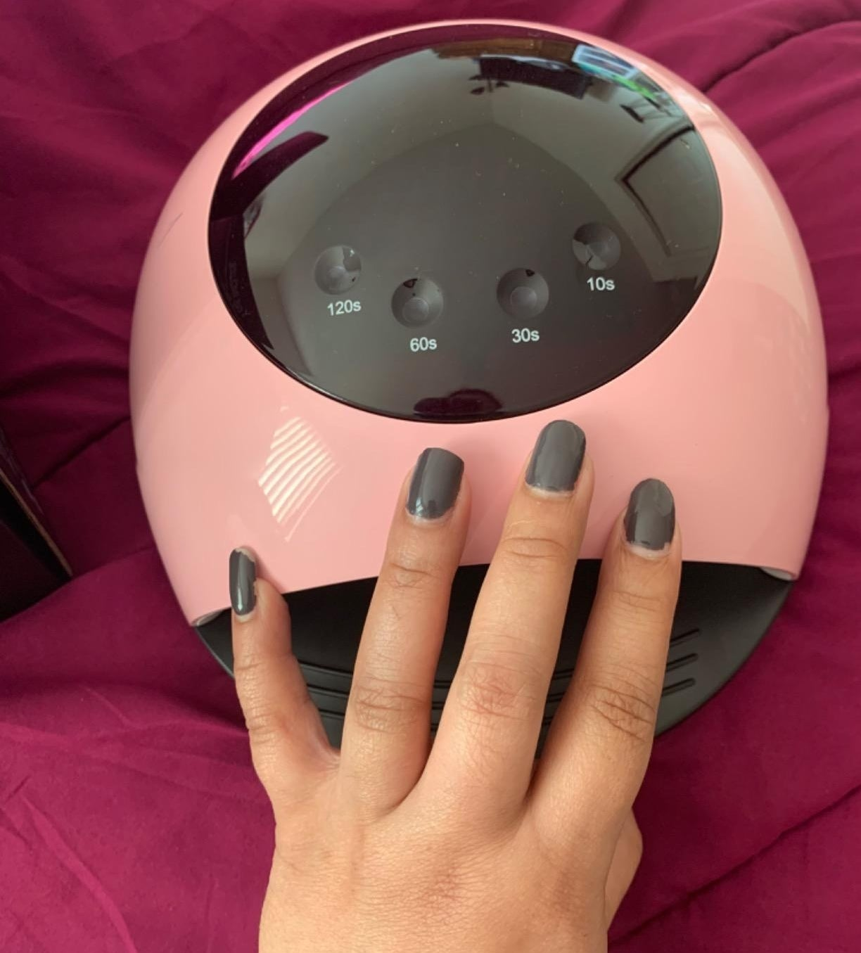 Freshly done nails placed on top of drying lamp