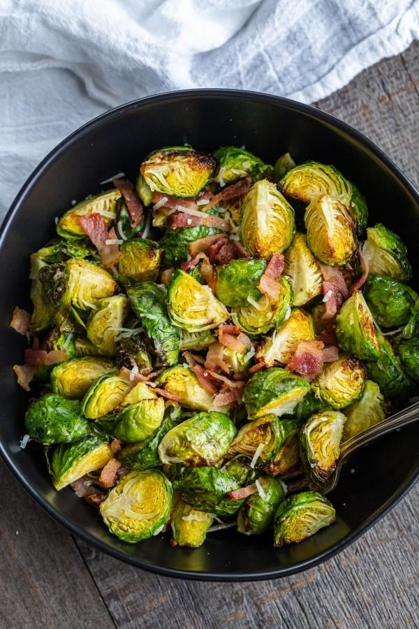 A bowl of Brussels sprouts with pieces of bacon and Parmesan.