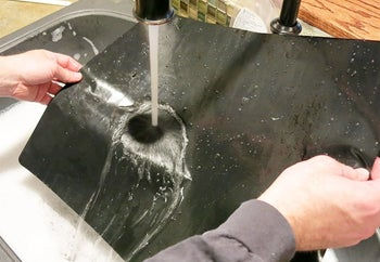 A model washing off one of the oven liners in the sink