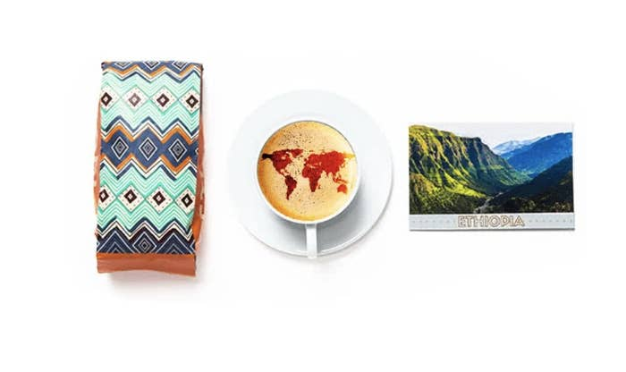 3 items sit against a white background: a colorful bag of coffee, a cup of coffee with a world map designed into the foam, and a postcard of Ethiopia
