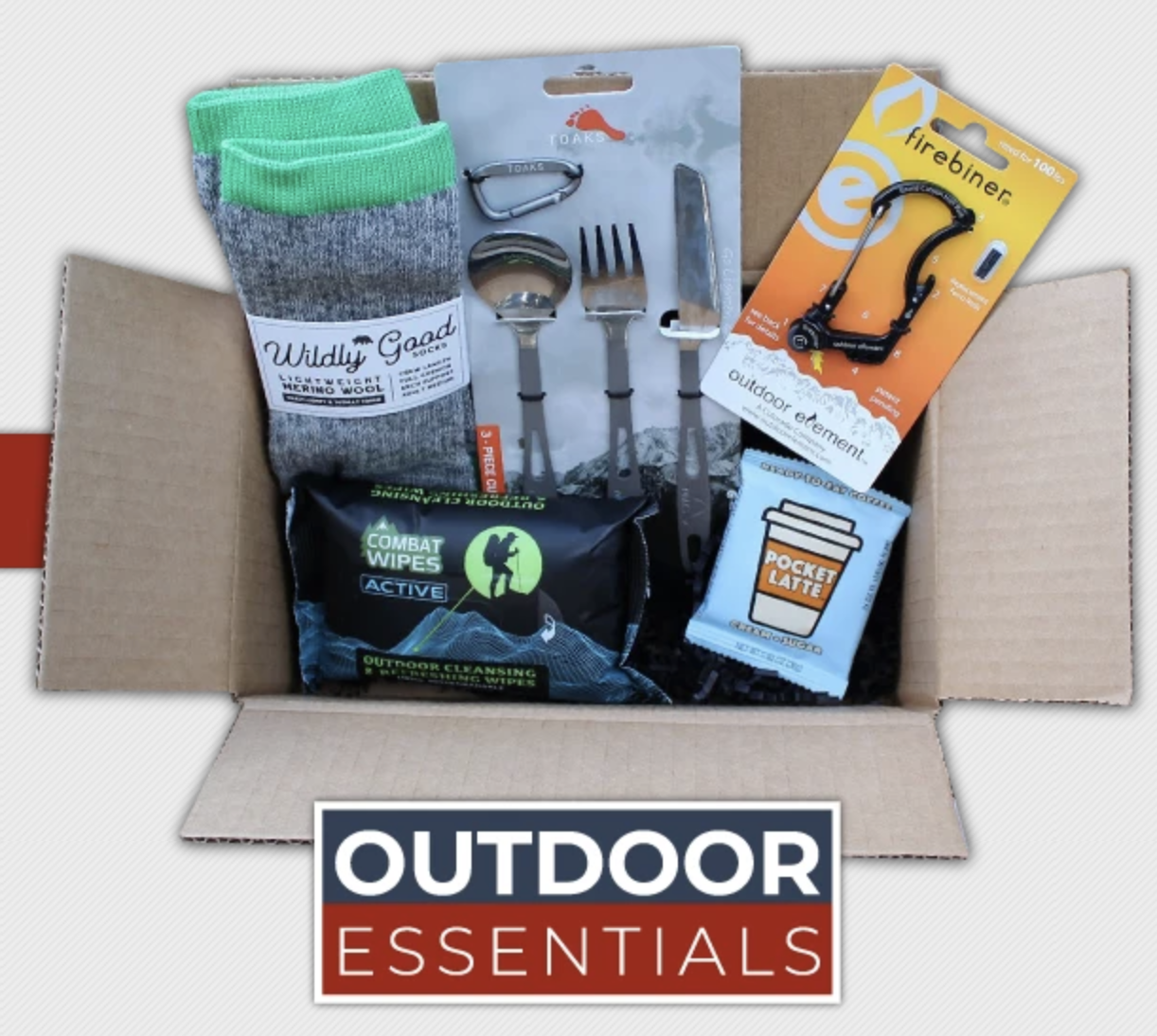 A top down of an open box stuffed with camping gear, like socks, utensils, wipes, and snacks