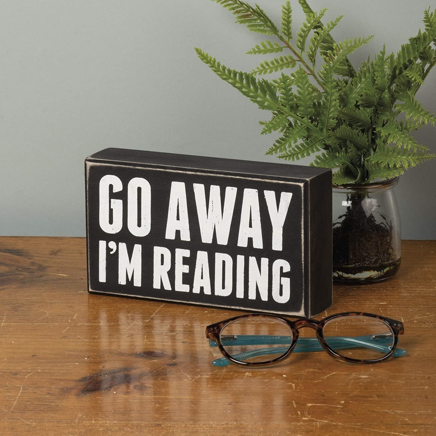 the sign on a table that says go away I'm reading