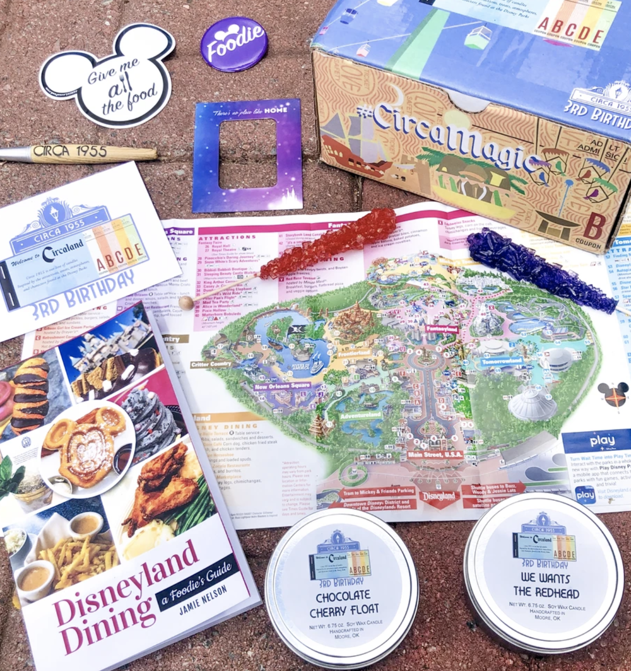 A collection of Disney items sit atop a brick floor, including a map, candles, rock candy, and a disney dining guide
