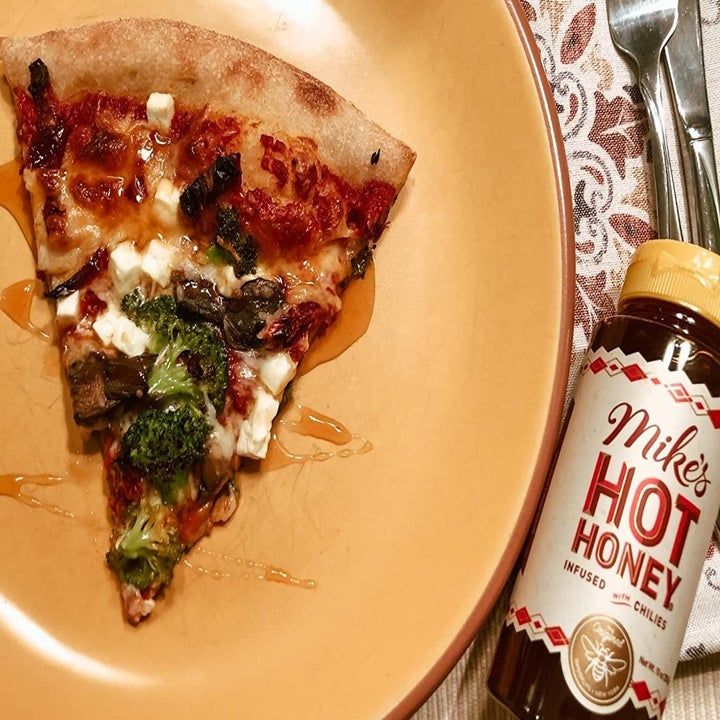 A reviewer photo of a piece of pizza drizzled with honey sitting next to a bottle of Mike's Hot Honey