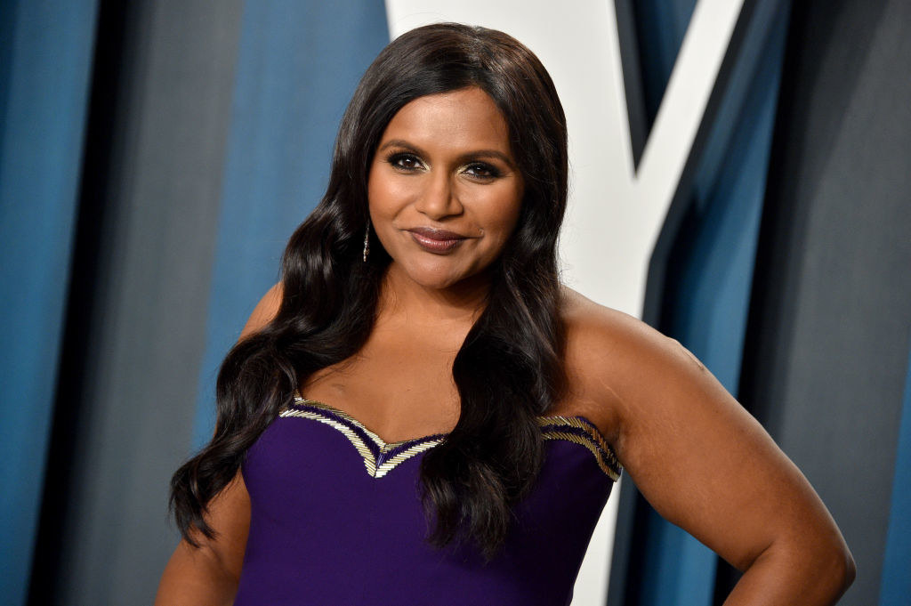 Mindy grinning in a dress with a sweetheart neckline