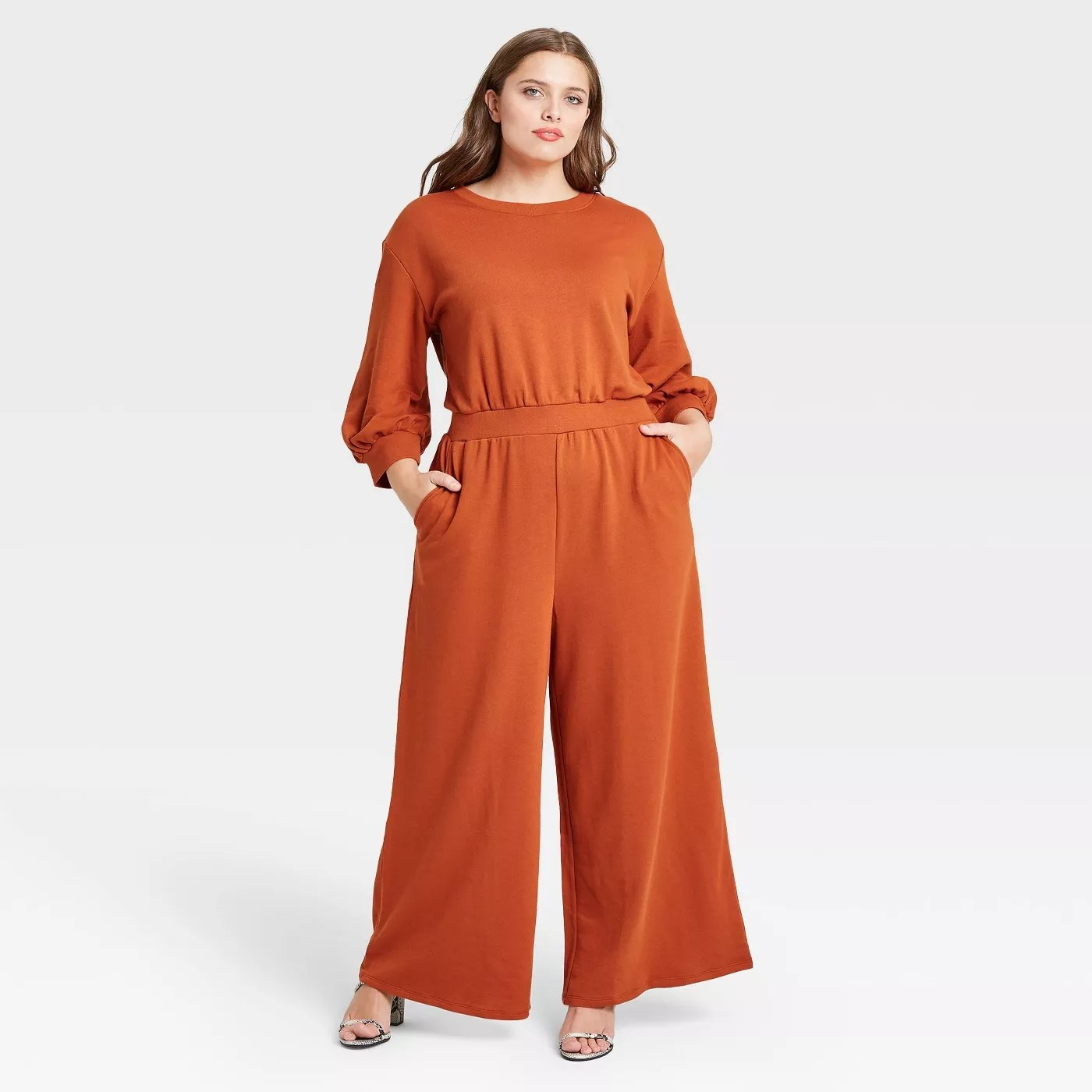 Orange cotton jumpsuit with a stitched waist. This is paired with open toe heels.