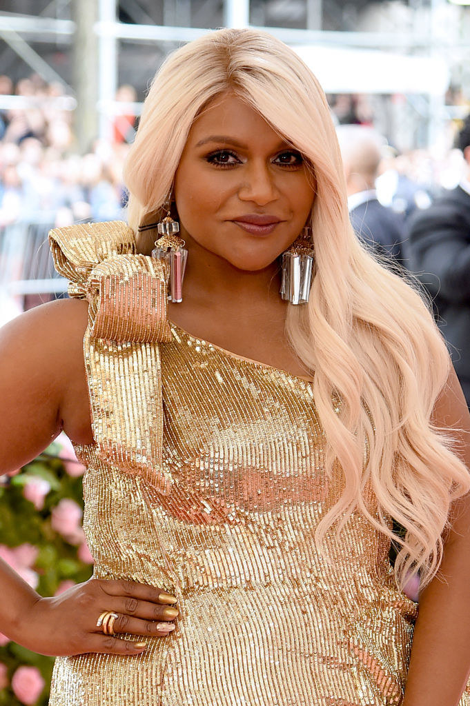 Mindy grinning in a metallic dress and wig