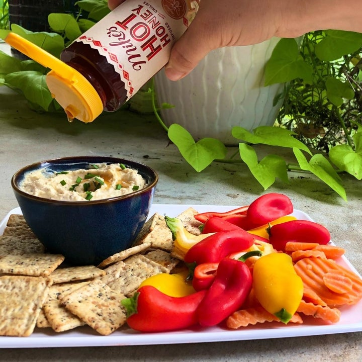 A reviewer photo of a hand drizzling honey in a bowl of hummus sitting next to a spread of peppers and crackers