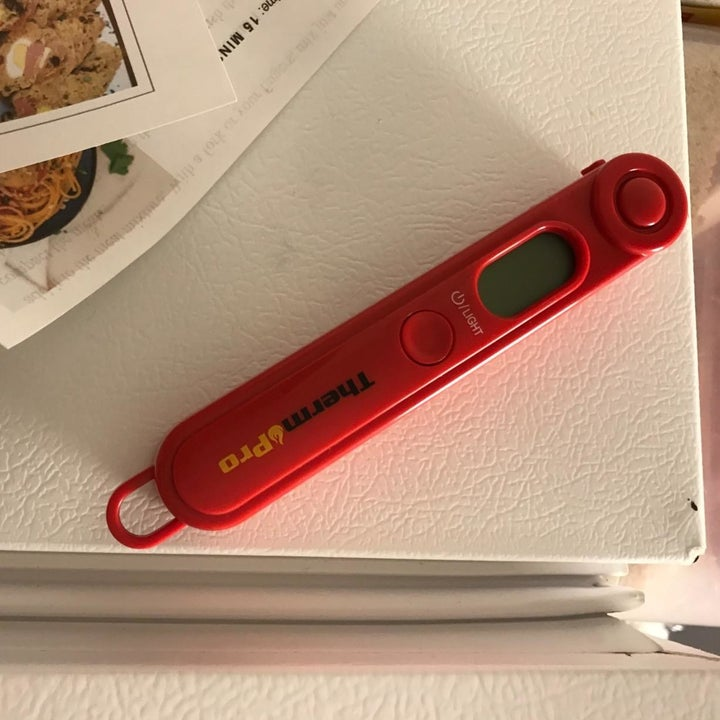 A reviewer photo of the red meat thermometer sticking to the refrigerator