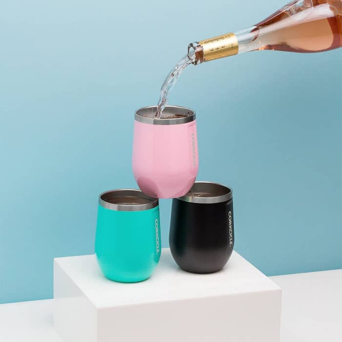 Three corkcicle stemless glasses being poured into