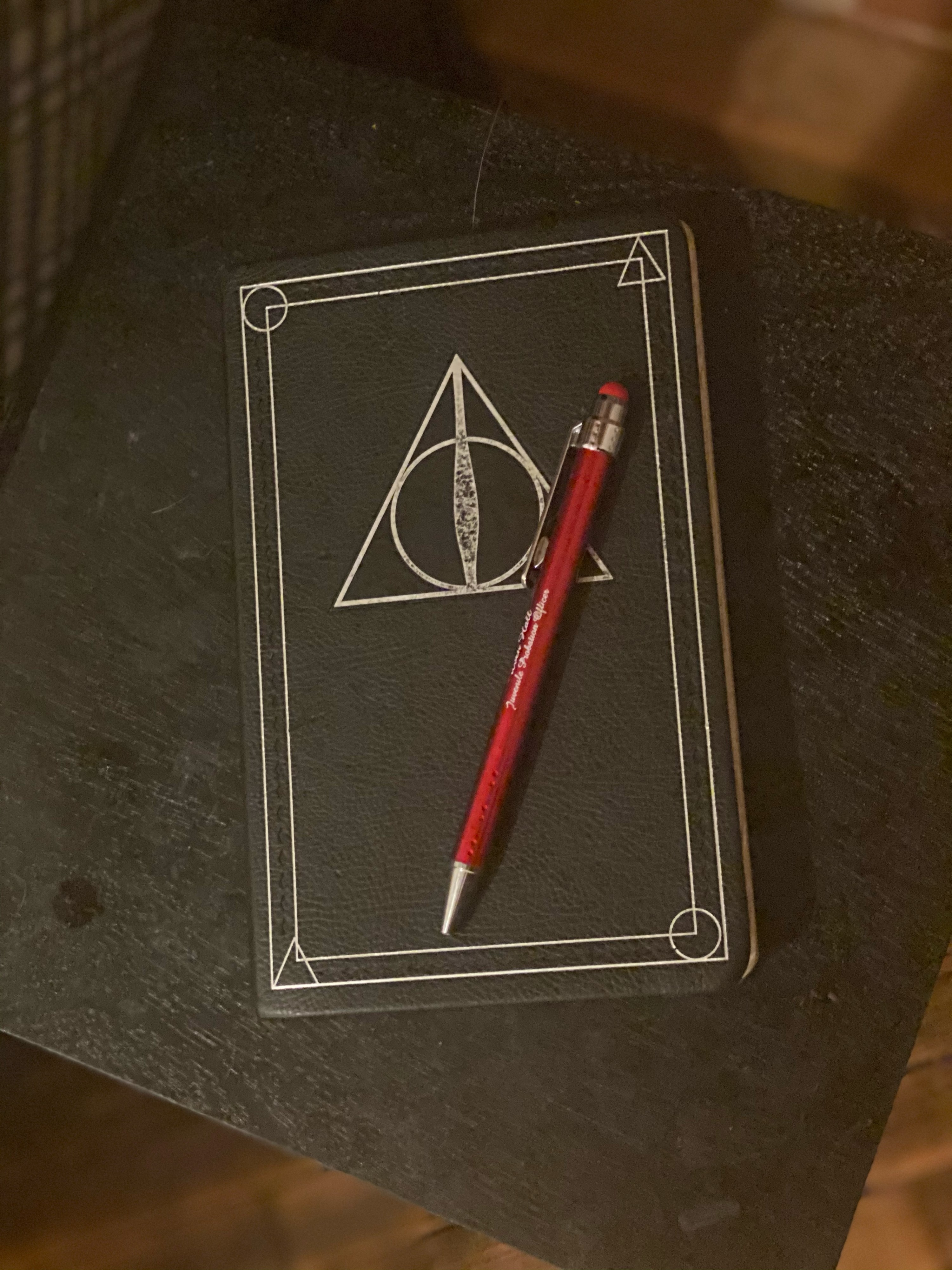 A red pen sit on top of a black Harry Potter themed notebook.