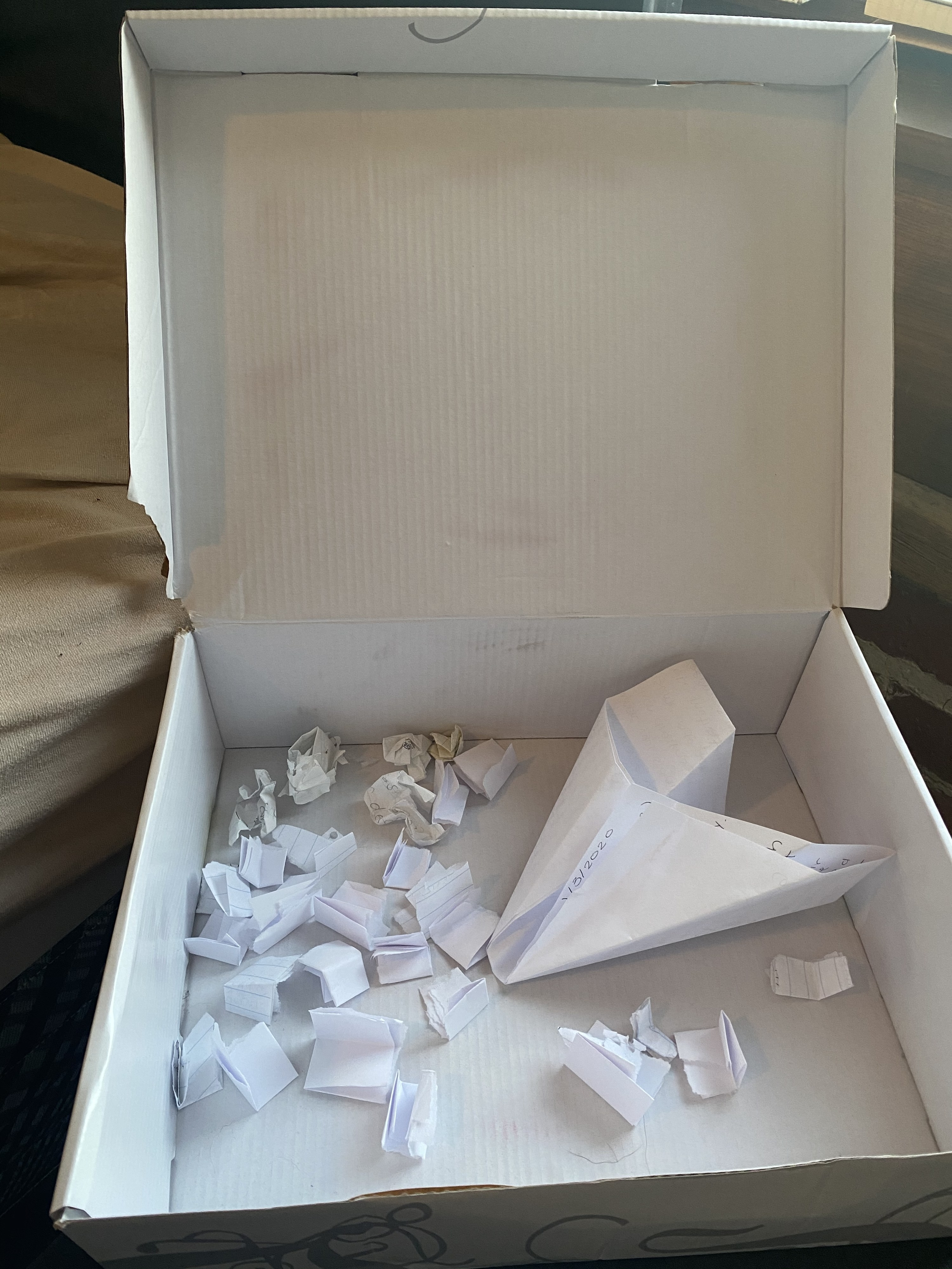 A white shoebox is filled with multiple pieces of folded up paper.