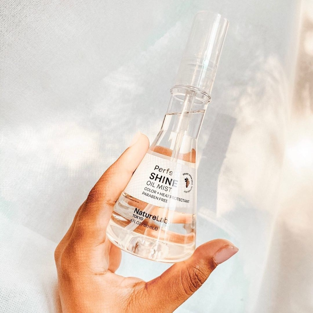 hand holding clear bottle of shine mist