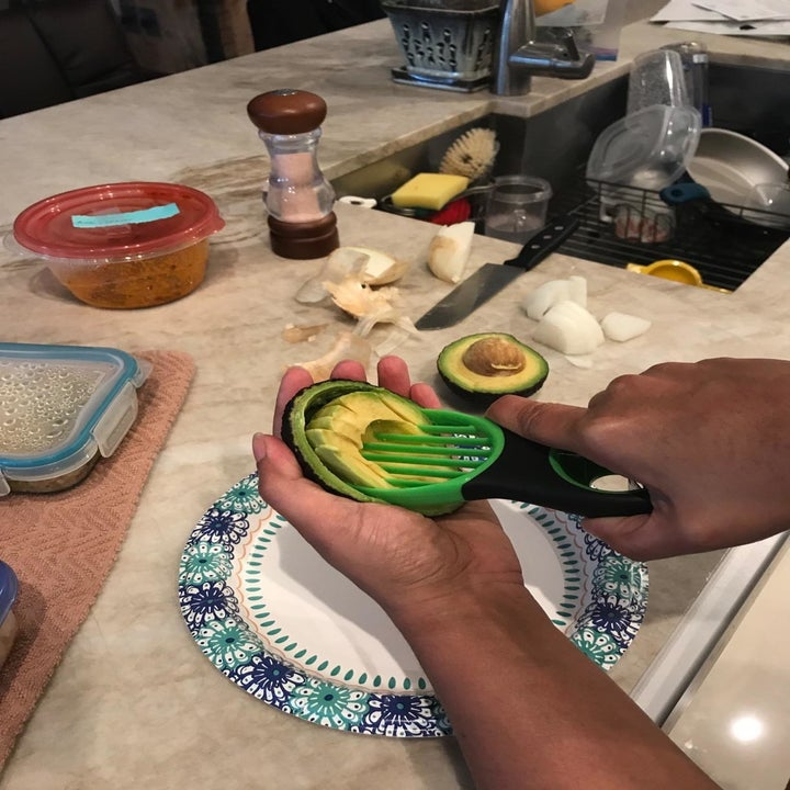 A reviewer photo of a hand using the 3-in-1 tool to cute an avocado into multiple slices