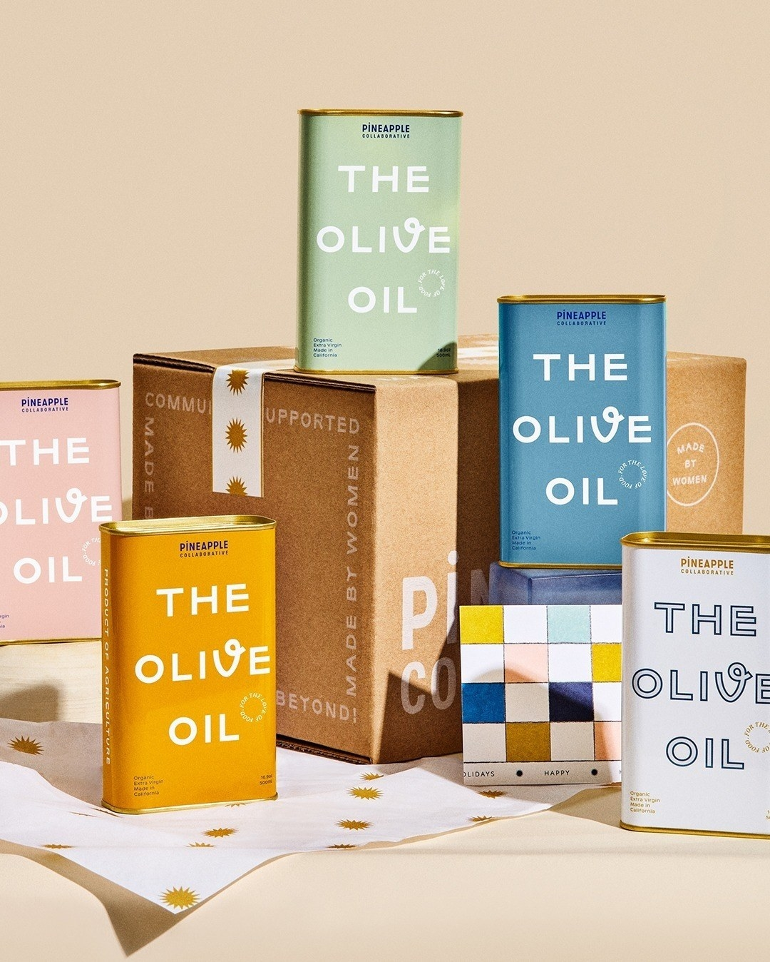 the tins of olive oil in yellow, pink, blue, mint green, and white