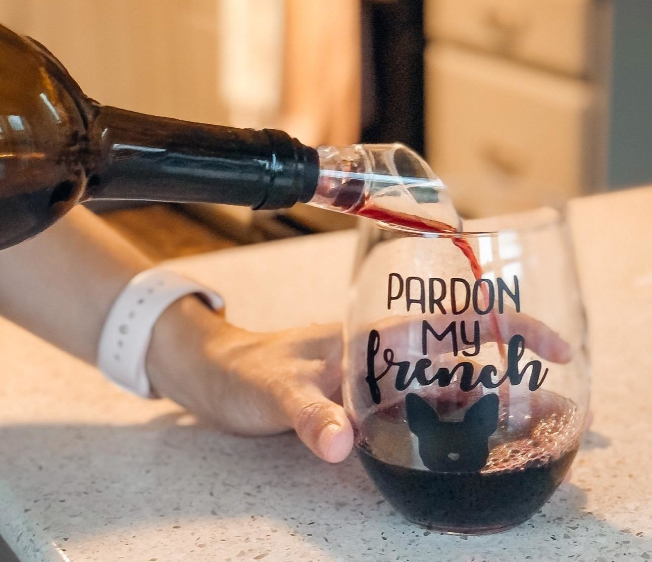 "A reviewer photo of a hand pouring a bottle of wine with an aerator stuck in the top into a wine glass that says ""Pardon my french"" with an image of a French Bulldog head"