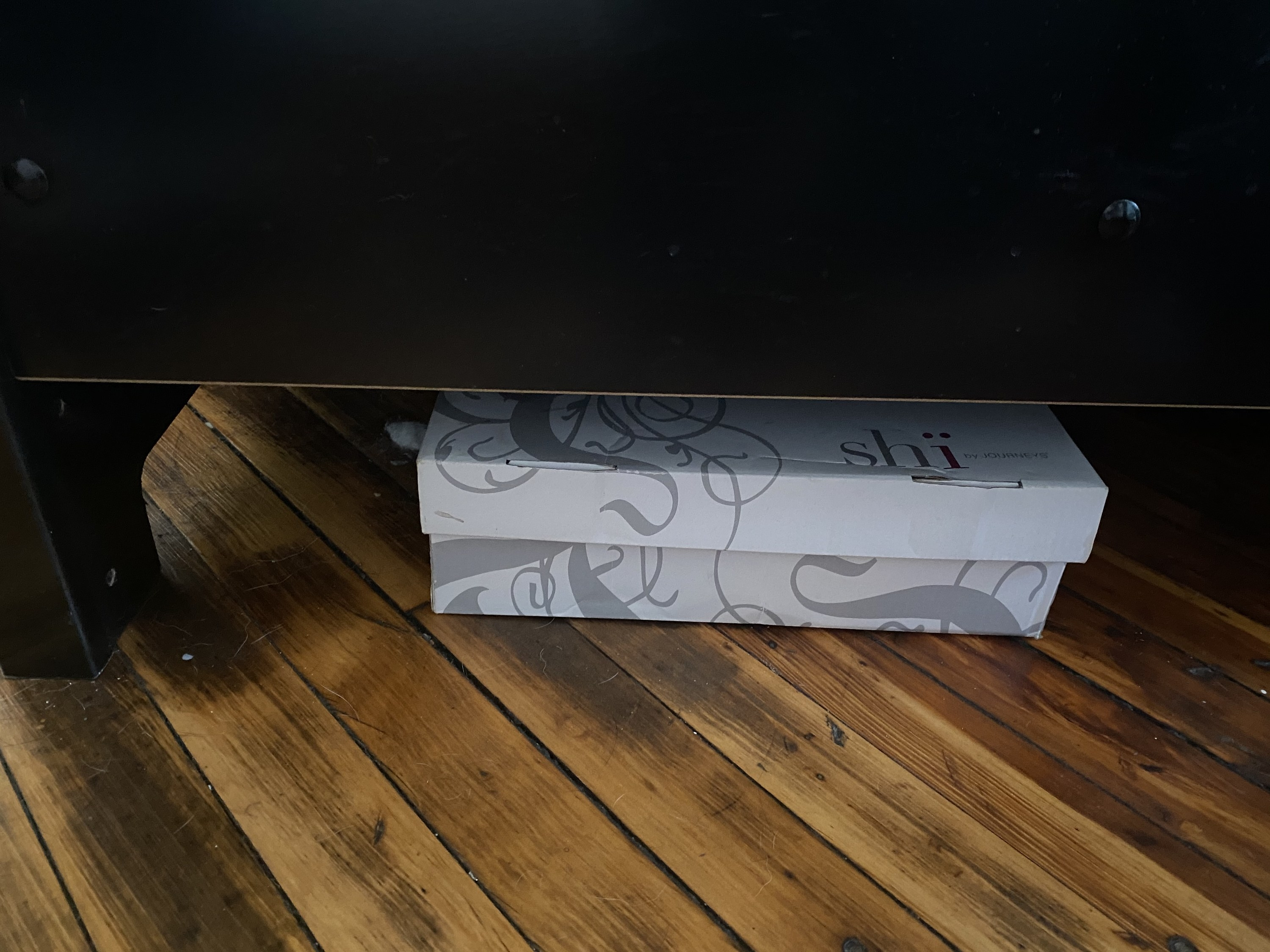 A white shoe box sits on a hardwood floor underneath a bed.