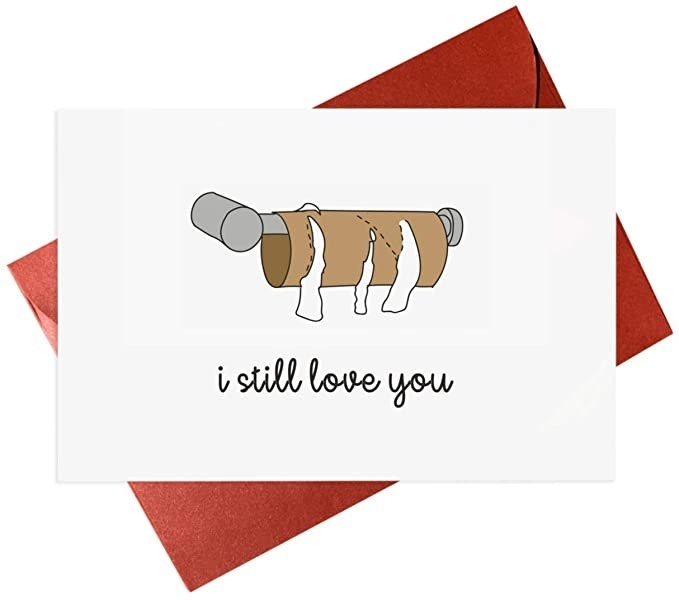 """A white card with a color drawing of a toilet paper roll with all the paper gone, and """"i still love you"""" written in black cursive below"""