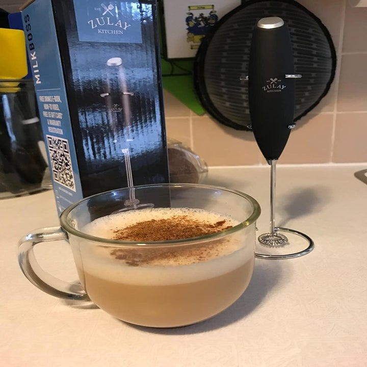 Reviewer photo of the handheld milk frother, the box it comes in, and a clear mug filled with a coffee drink topped with foamed milk