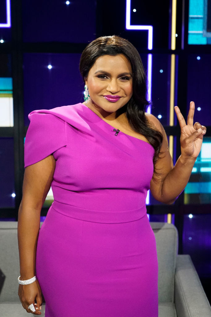 Mindy throwing up the peace sign with her hand