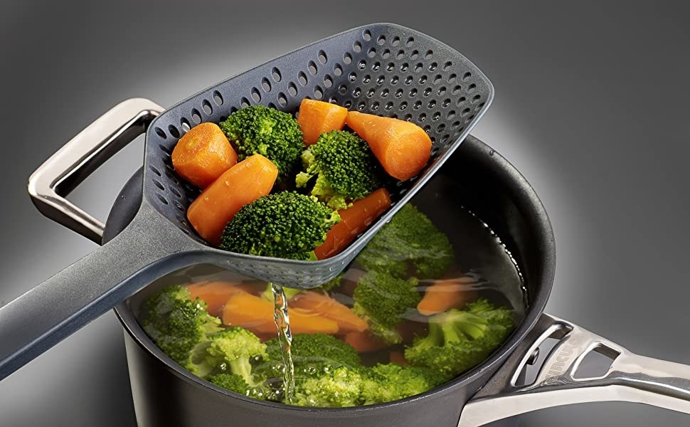 A spoon with drainage holes scooping vegetables out of a pot full of water and vegetables