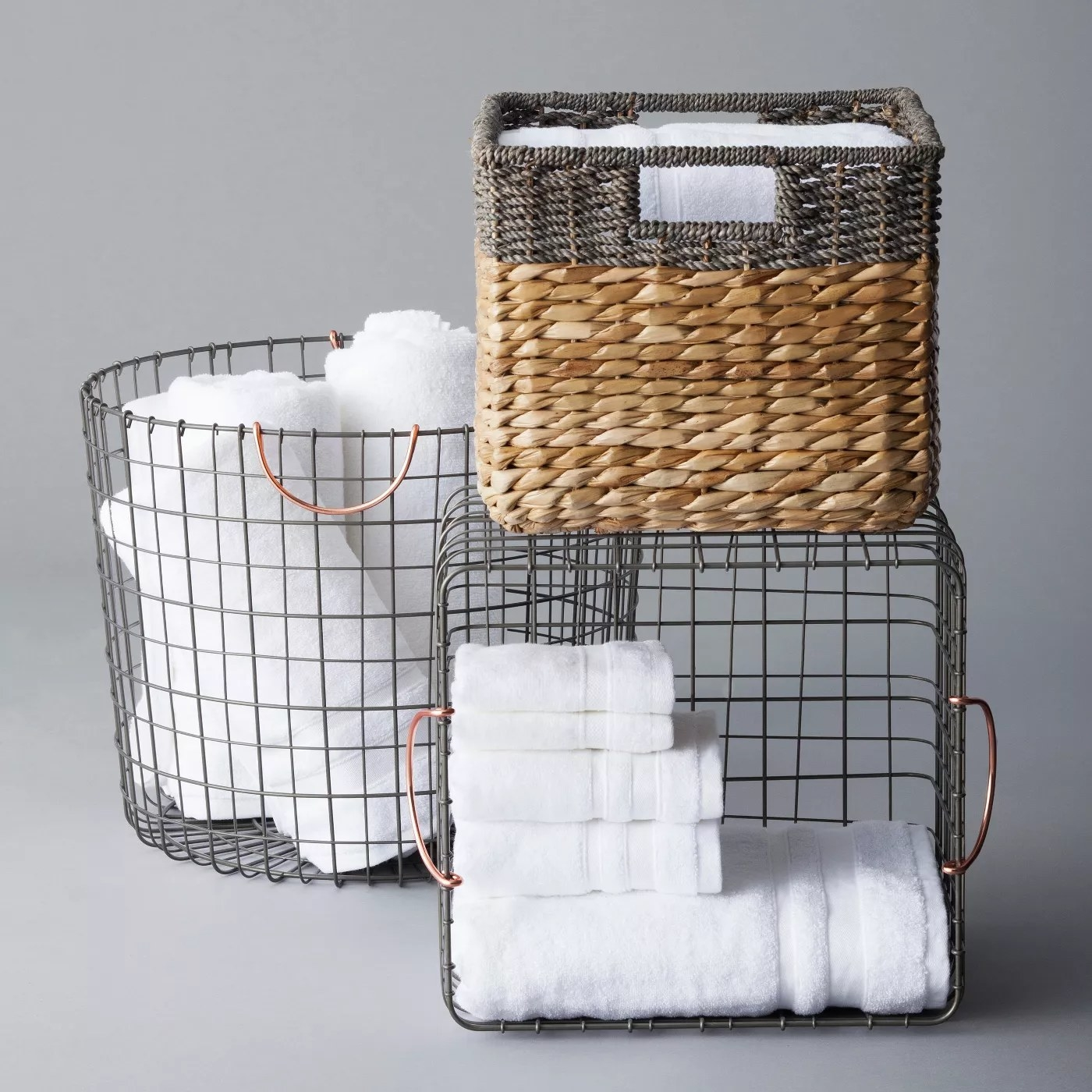 The basket holds folded bath towels and is displayed with two other types of baskets