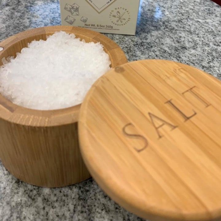 "A reviewer photo of a wooden spice container filled with the salt with an attached lid engraved with the word ""salt"""