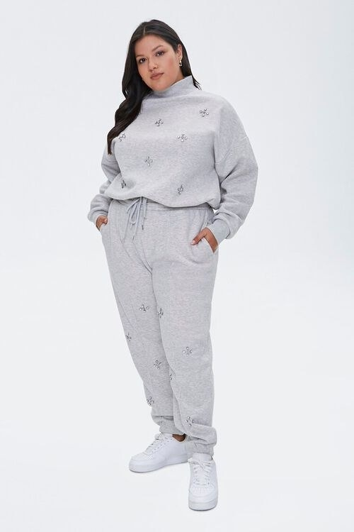 Model wearing grey pullover and jogger set encrusted in faux gems