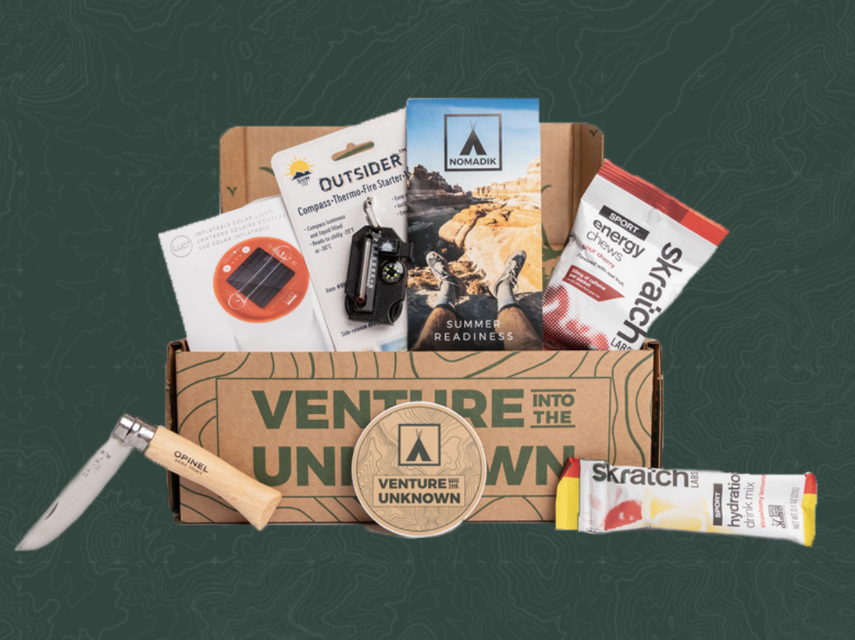 An open cardboard box with items like a camping knife, fire starter, energy chews, and more against a dark green background
