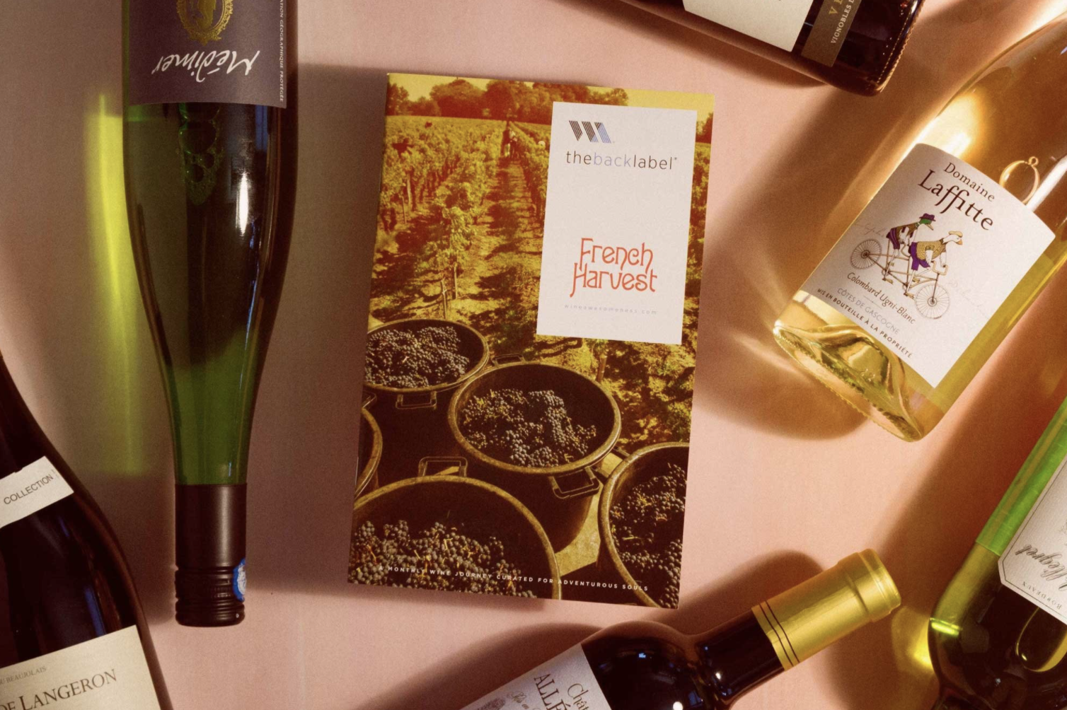 A top down of a booklet called French Harvest surrounded by bottles of wine