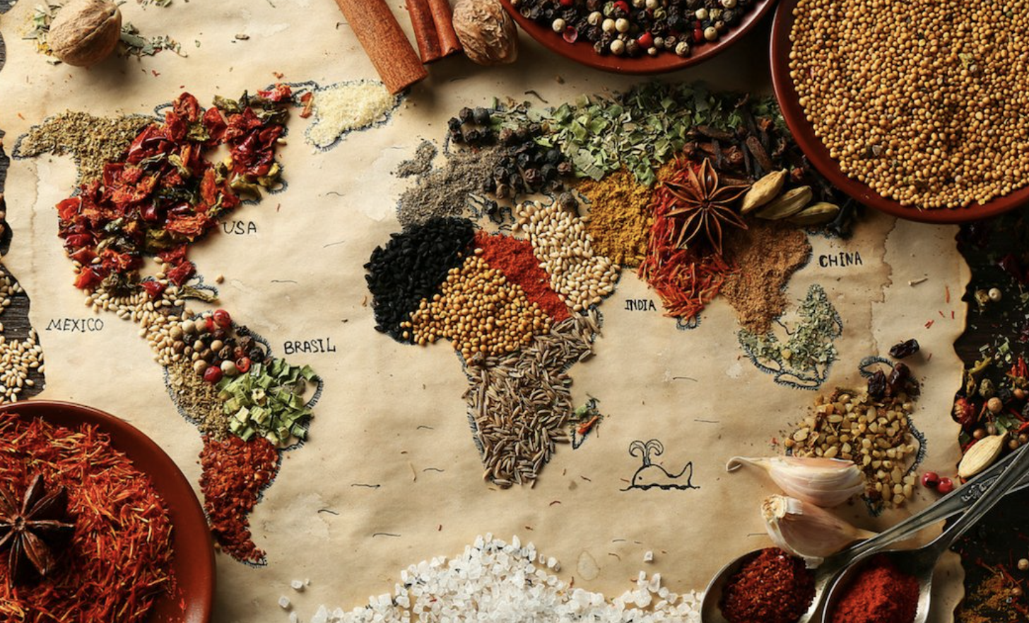 A variety of colorful spices in the shape of a global map across brown paper, with bowls of spices surrounding