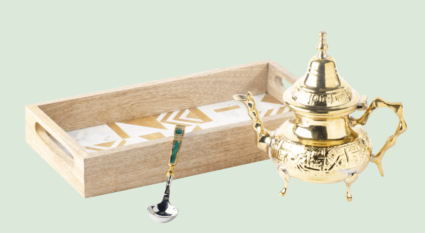 A wooden serving tray, intricate gold tea pot, and fancy serving spoon against a teal background